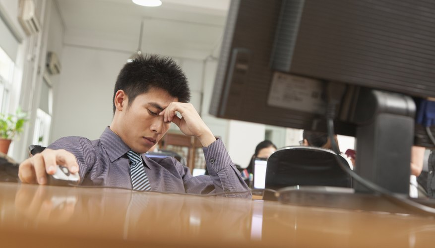 exhausted businessman sitting in front of computer