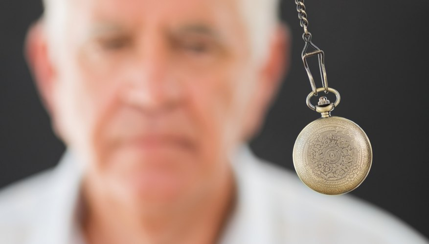 Elderly man watching swinging pendulum