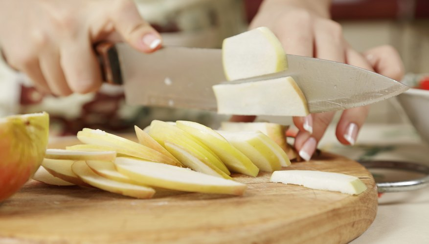 A woman is slicing an apple.