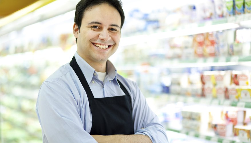 Smiling store keeper in his supermarket