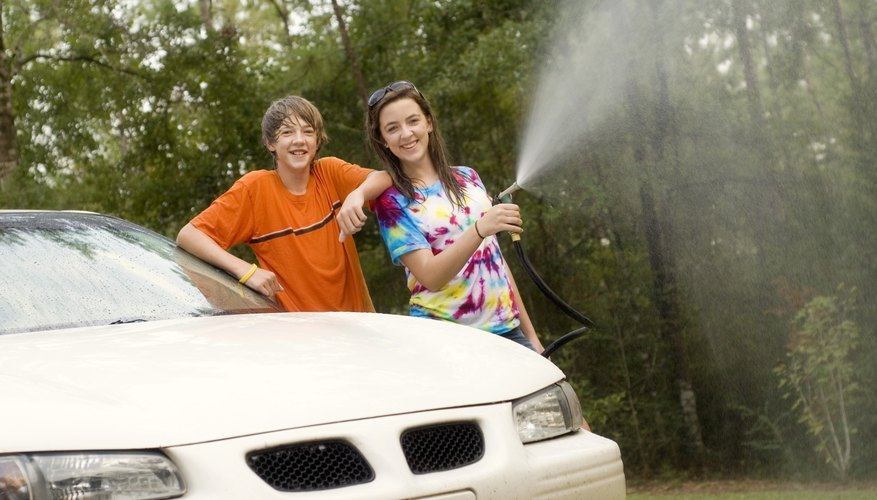 Two teenaged siblings washing a car together.