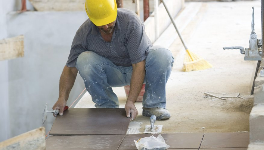 A builder laying tile on a construction site.