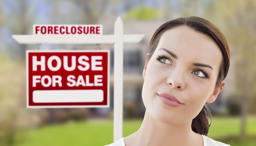 Woman in front of foreclosure house for sale sign