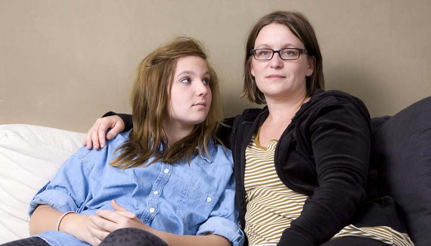 A mother talking to her daughter with her arm around her on the couch.