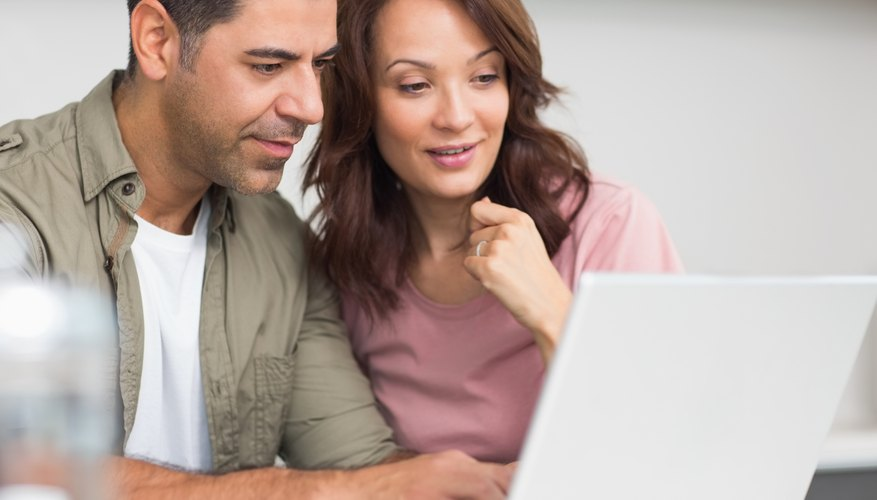 Couple of home owners reading on laptop