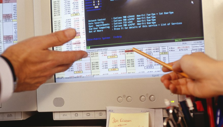 Two people viewing computer screen in trading room