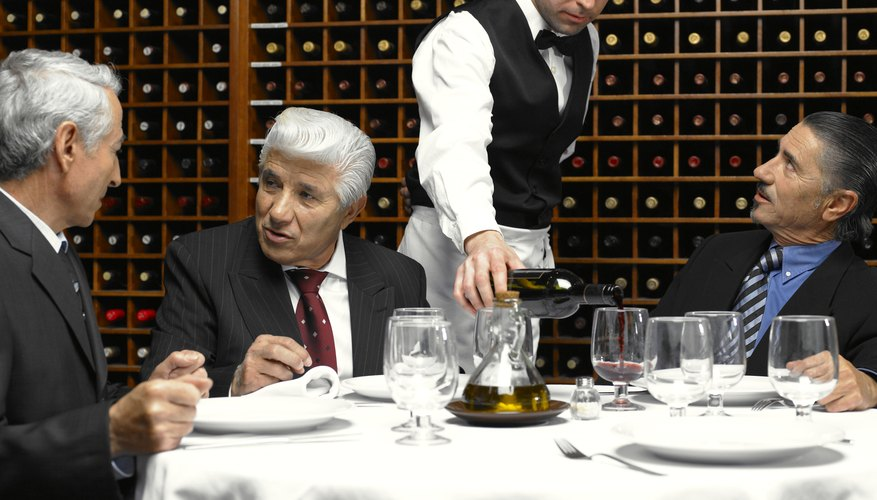 Waiter serving wine to businessmen in restaurant