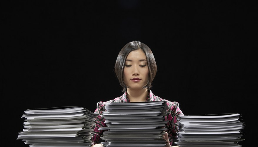Woman sitting at desk in front of stacks of documents