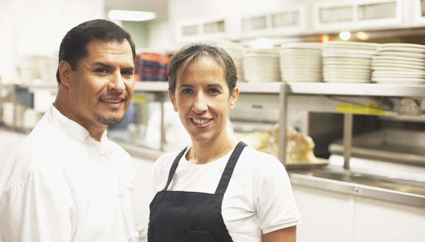 Portrait of a male chef smiling with a female chef