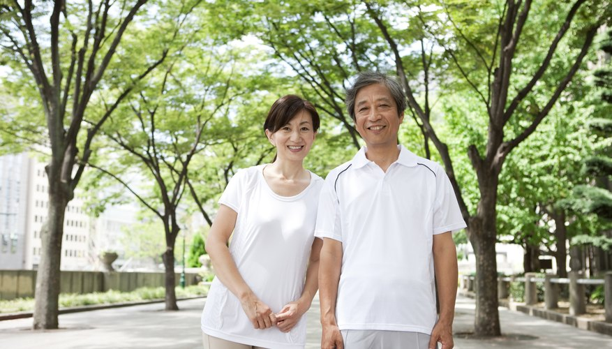 A retired couple standing in a park outside.