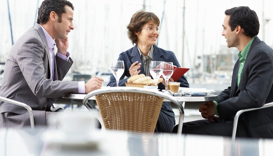 Three business people outdoors at table in restaurant