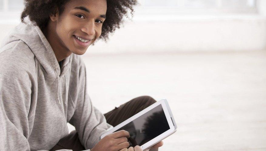 Smiling teenage boy holding tablet
