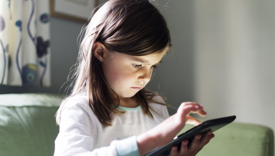 A young girl using a smart tablet at home.