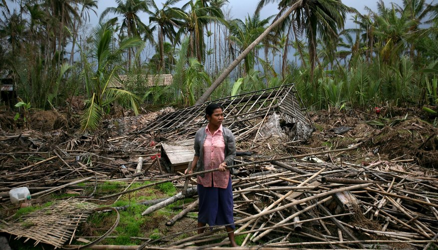 A woman picks through the wreckage of her home at the isolated village of Myasein Kan on May 20, 2008 in Myanmar.