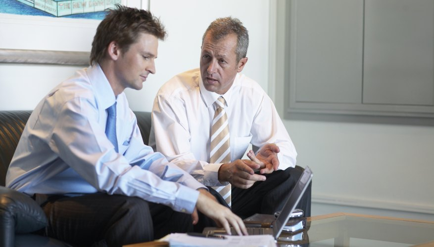 Two businessmen having discussion on sofa in office waiting area