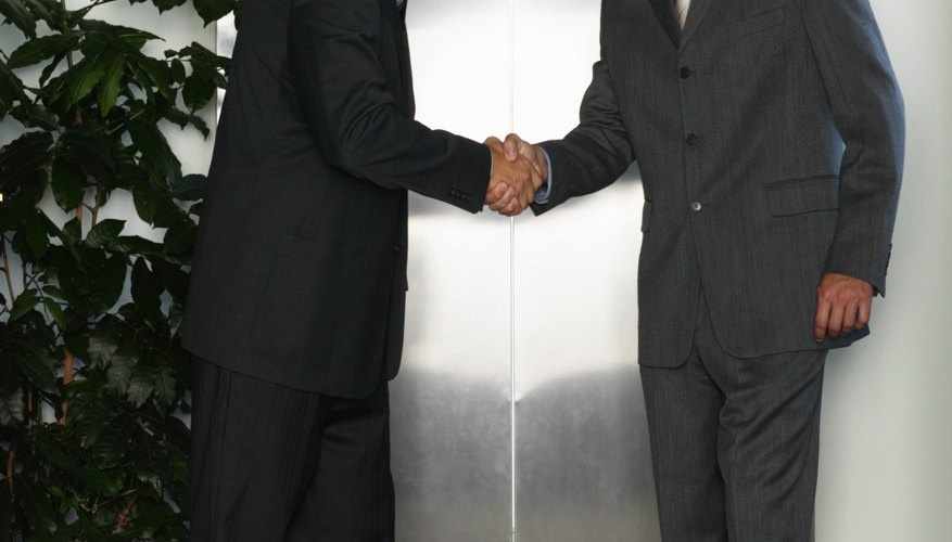 Two businessmen shaking hands by elevator