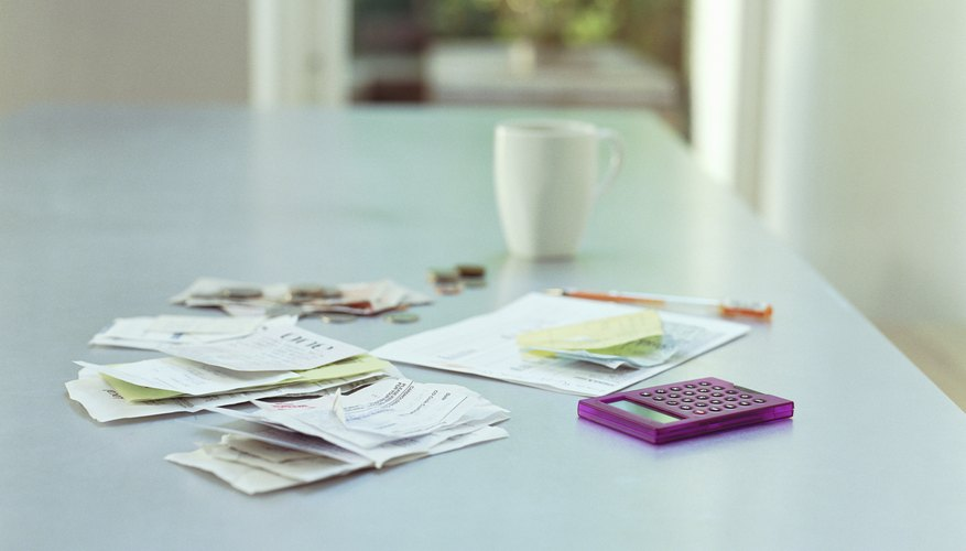 Receipts, money, a document and calculator on a desk.