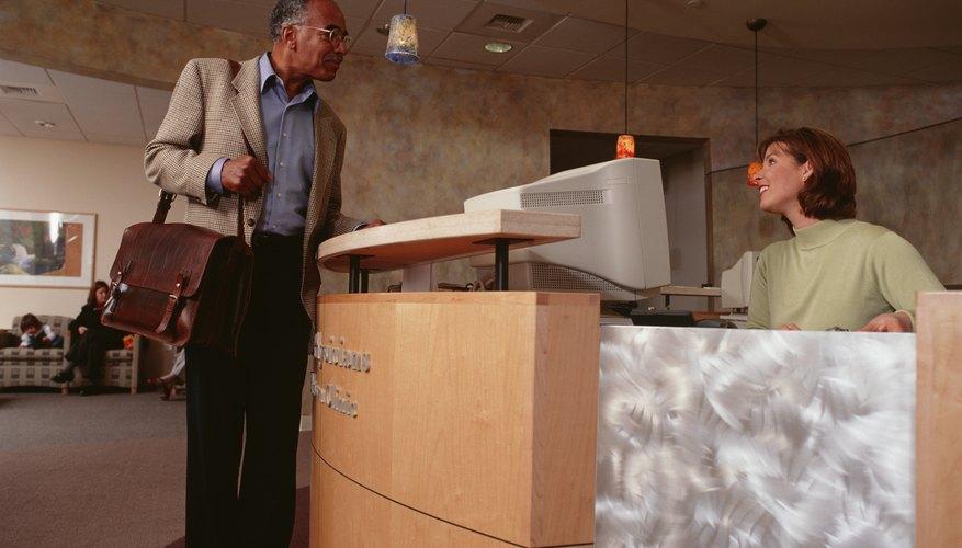 Senior man talking to receptionist at clinic reception