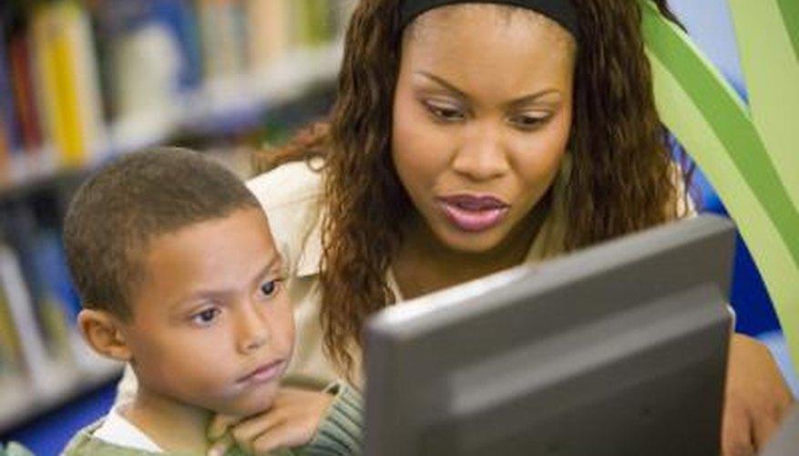 Maestra con un estudiante en la computadora.