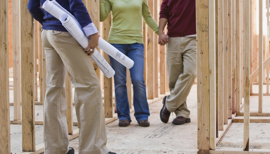 People are walking through a house being built.