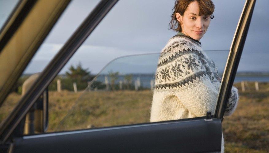 Woman standing by open car door, Iceland