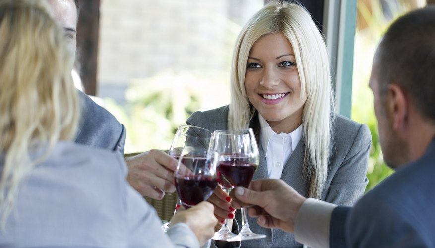 Business people are toasting over a glass of wine.