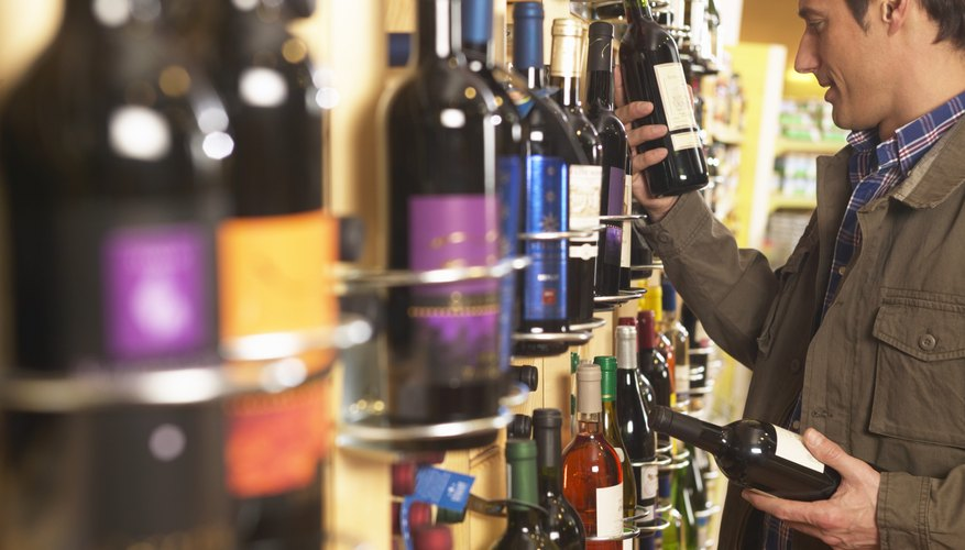 A man shops for wine at a supermarket.