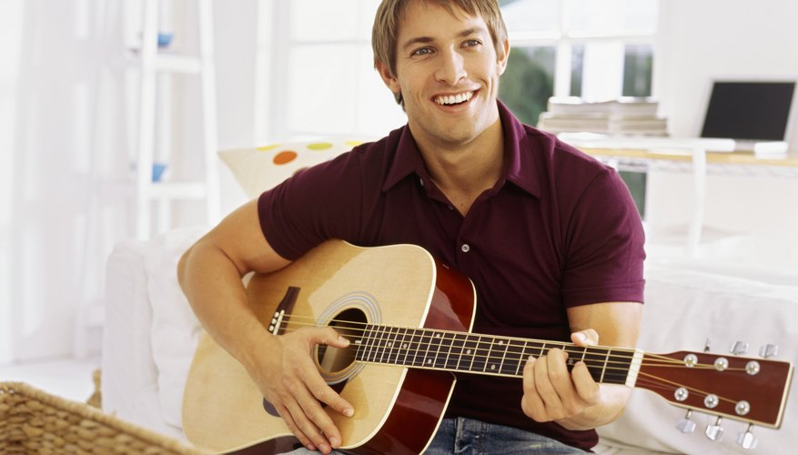 A smiling man is playing the guitar.