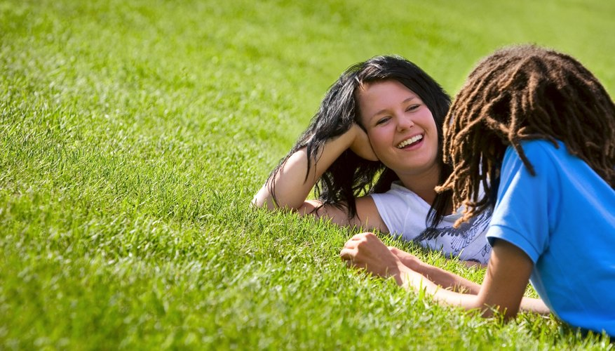 Mother and child laying on grass lawn.