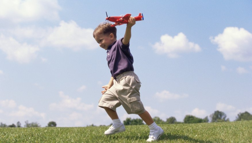 Kid playing with toy airplane on the grass.