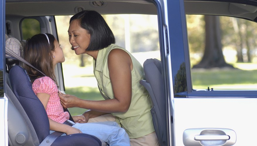 Mother buckling daughter into car seat