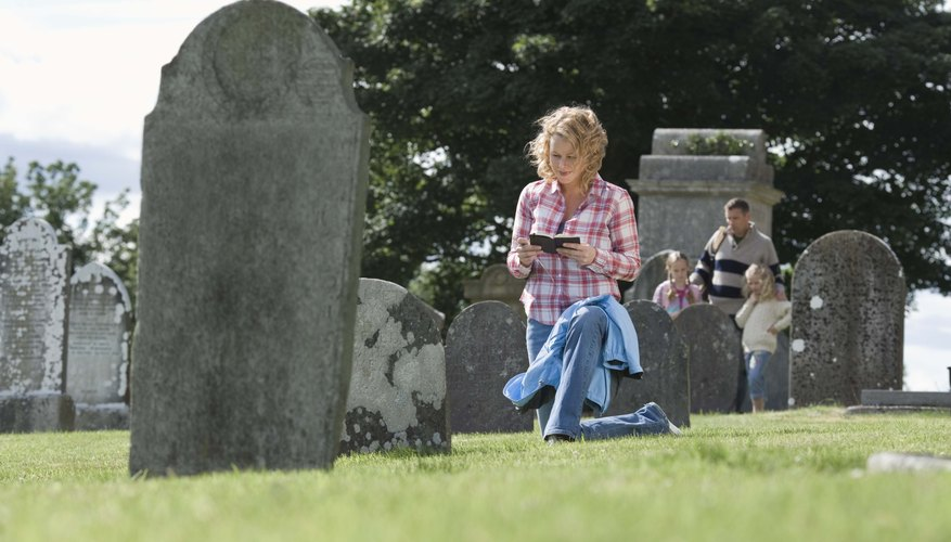 Woman transcribing epitaph from gravestone