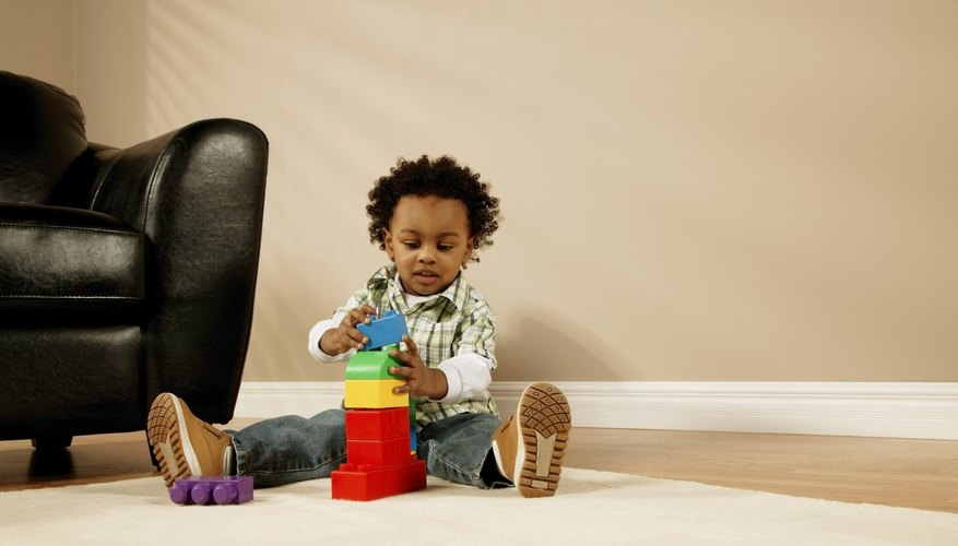 Three year old playing with blocks in living room.