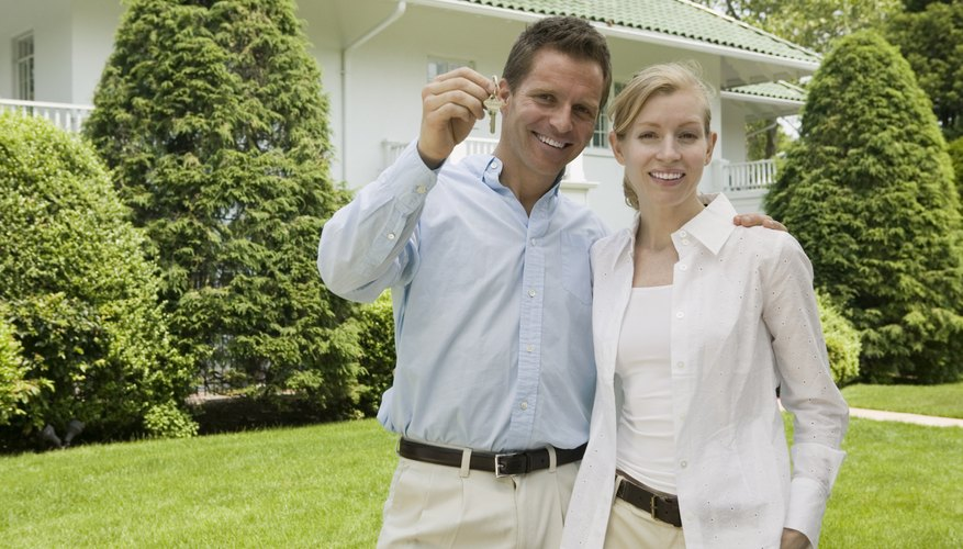 Couple standing in font of a newly purchased home.