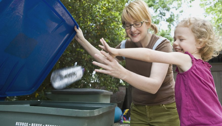 Two siblings tossing a plastic bottle into a recycling bin.