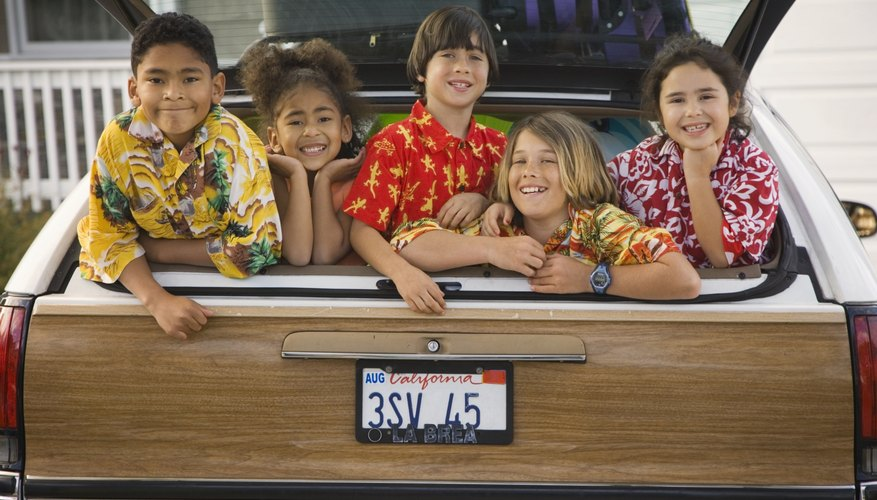Five kids smiling in the back of a station wagon.