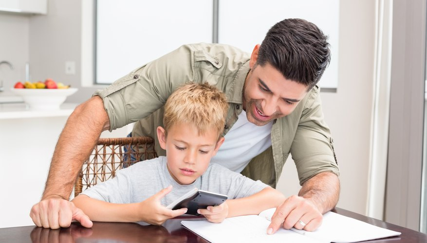 Image of father and son doing a math problem.
