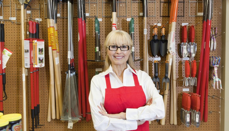Portrait of a happy senior woman with arms crossed in front of gardening tool