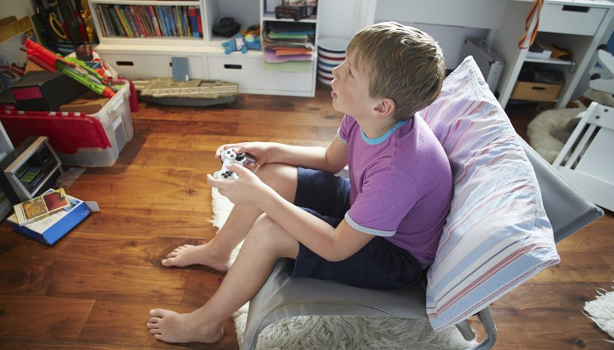 Boy holding a remote control joystick for a PlayStation.