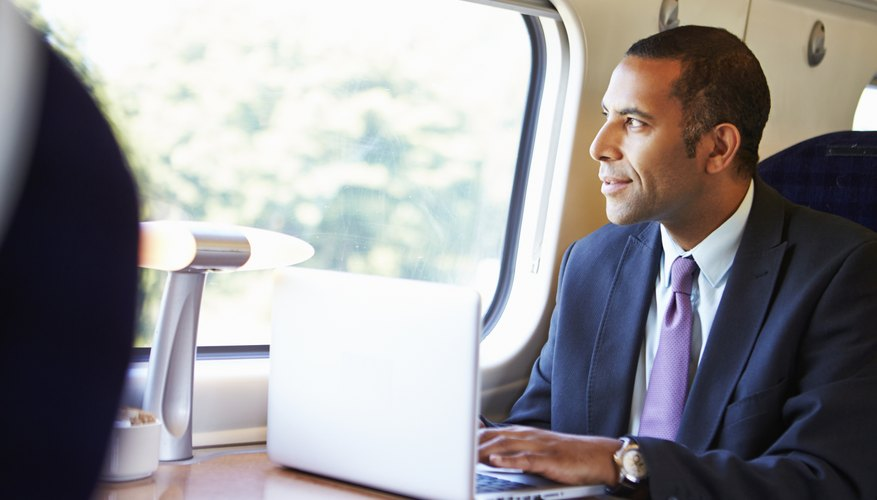 Businessman Commuting To Work On Train And Using Laptop