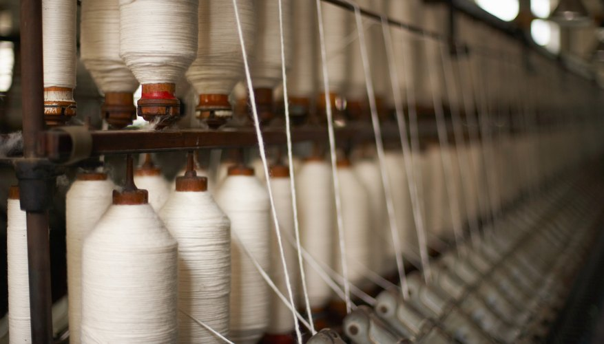 Spools of thread on machinery in textile mill
