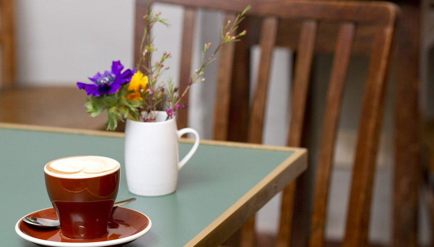 A mug of spring flowers on a coffeehouse table.