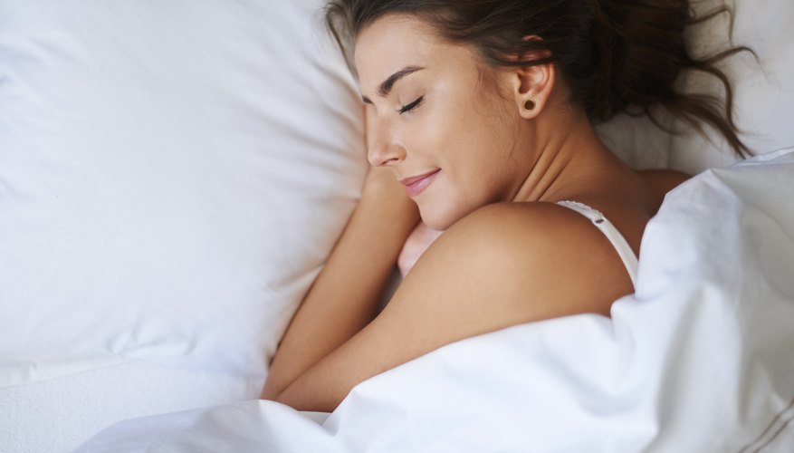 Woman resting her head on pillow in bed.