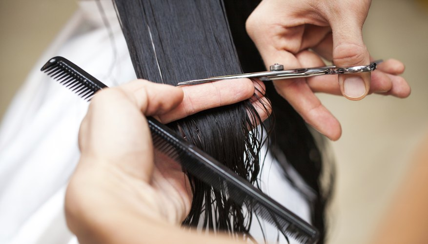 stylist cutting woman's hair in salon