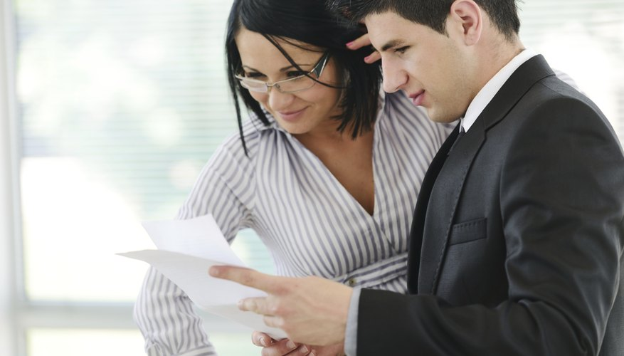 Businessman and businesswoman reading a report at workplace