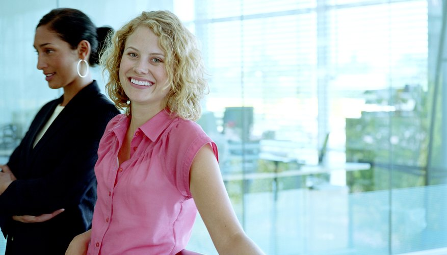 Woman standing with female colleague in office, smiling, portrait