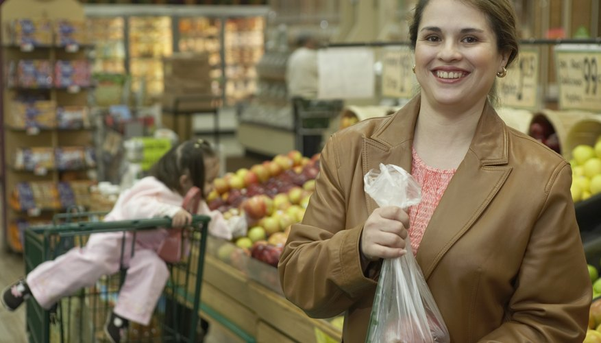 A woman holding a bag of apples in the produce section.