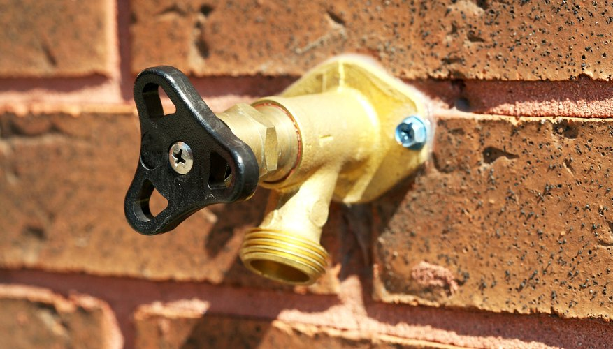 Water tap and valve on brick wall