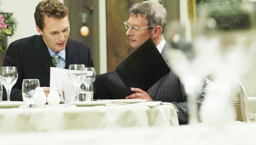 Two businessmen in restaurant looking at paperwork