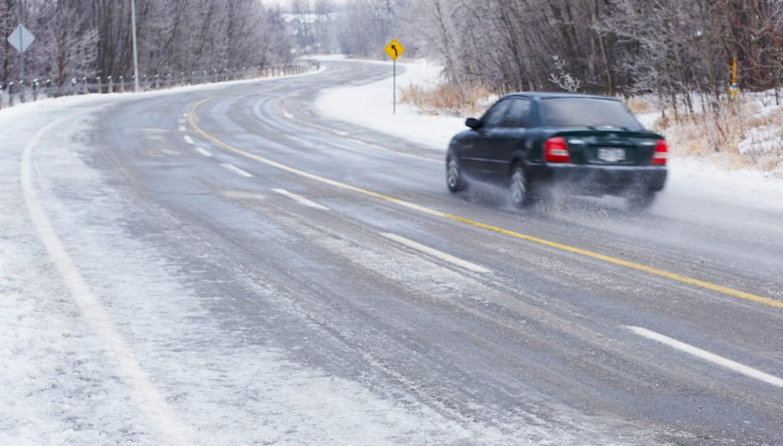 Car driving on icy rural road in Ontario, Canada